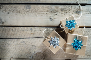 Three craft cardboard  gift boxes on a rustic wooden background. Gift kraft boxes with ribbon bow and rope.
