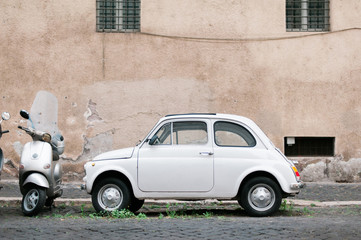 An Old White Car and Modern Scooter on the Streets of Rome, Italy