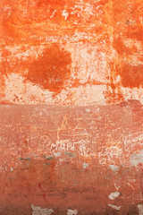 Shabby Orange Wall With Lots of Names Scratched in