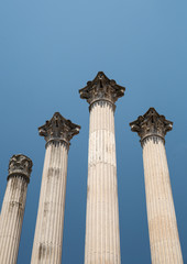 Roman pillars towering against a bright blue sky