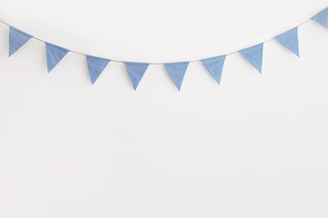 Blue and white striped bunting hanging against a white wall