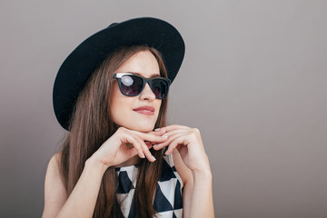 Young beautiful fashionable woman with trendy makeup  in black hat and glasses on the grey background . Model looking at camera, wearing stylish eyeglasses. Female fashion, beauty concept.