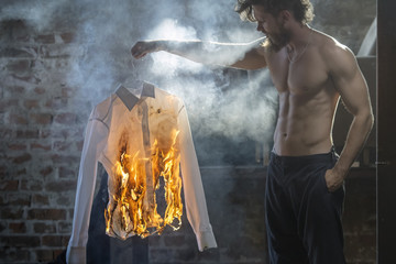 change, tired of everyday life young hipster man burns a shirt,refuse to accept