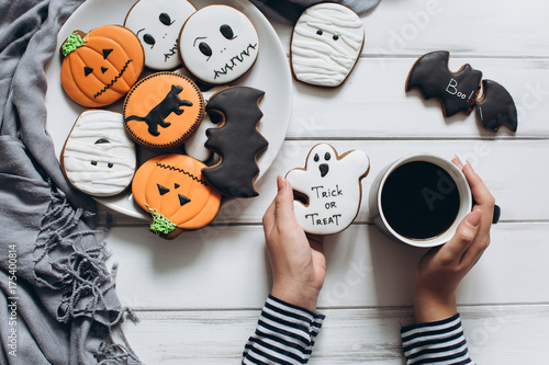 The girl preparing for Halloween, drinking coffee and eating scary gingerbread cookies.