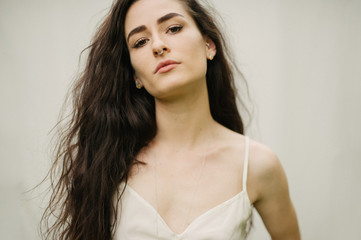 Female with long curly dark hair and septum nose piercing with cream background and cream romper