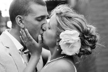 A black and white portrait of a bride and groom kissing on their wedding day