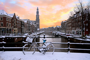 Poster Amsterdam Amsterdam covered with snow with the Westerkerk in winter in the Netherlands at sunset