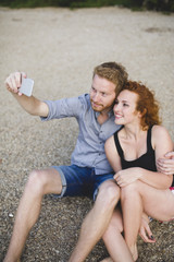 Ginger couple taking selfie with smart phone