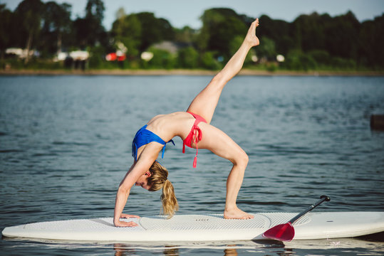 Young woman doing back bend on stand up paddle board.