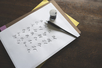 A Calligraphy Pen, Ink and Paper With The Modern Calligraphy Alphabet