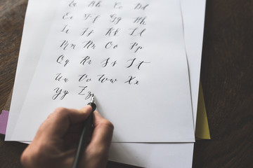 A Left Handed Person Writes The Alphabet With A Straight Calligraphy Pen