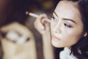 young asian woman applying make up