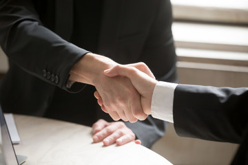 Close up of two business people shaking hands. Executive corporate representatives greeting each other, giving handshake to close good deal, welcoming new contract or agreement. Teamwork concept.