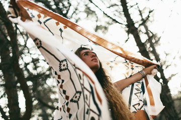 Young blonde woman flying a big scarf on the woods.