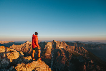 male hiker on top of a mountain overlooking the bavarian mountain range at sunrise