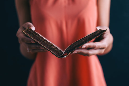 Closeup of a woman reading an old book.