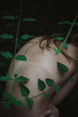 Naked woman in garden with vines at dusk