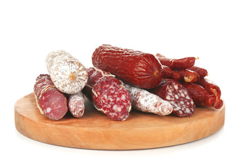 Assortment of sausages on wooden board, isolated on white
