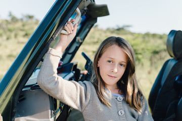 young girl in safari truck, looking to camera