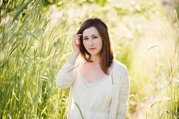 Beautiful young woman walking through sun lit tall grass.