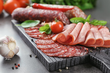 Delicious sliced sausages on wooden board