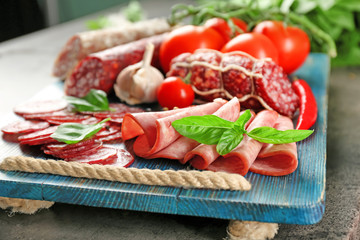 Fototapete - Delicious sliced sausages on wooden board