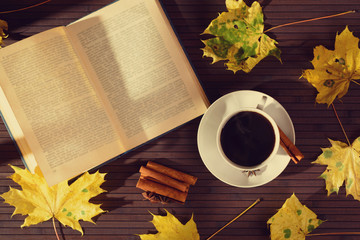 A hot Cup of coffee and old book, autumn maple leaves on the table