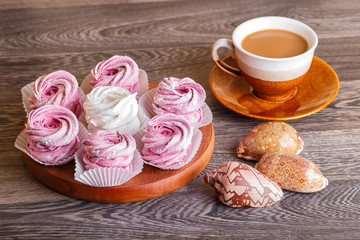 pink and white marshmallows (zephyr) on a round wooden board with cup of coffee and seashells