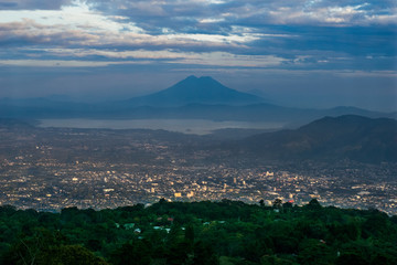 The city of San Salvador, El Salvador at sunset with the view of lake Ilopango and San Vicente Volcano, taken from San Salvador volcano