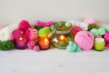 Yarn, candles, knitting on a white background wood. Pink and green colors.