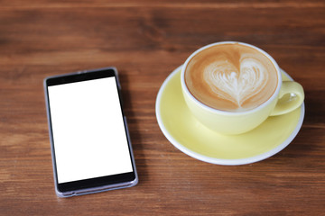 Coffee latte art heart shape in light green ceramic cup besides white smart phone with white black screen on wooden table background,mock up image