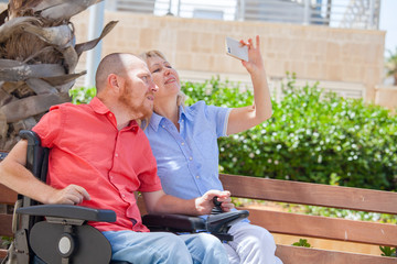 disabled man with his wife having fun taking selfie photos