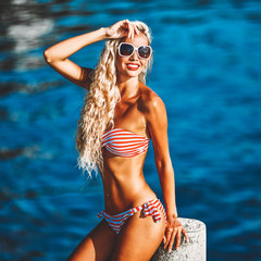 Summer portrait of blonde girl in bikini and sunglasses