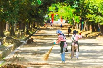 屋外を掃除する女性