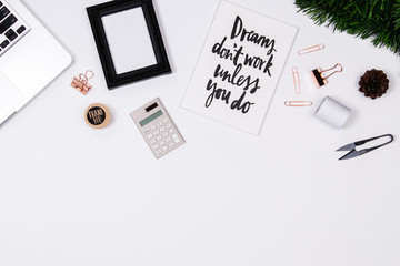 Home office desk workspace with laptop, quotes diary, golden paperclip, pine branches on white background. flat lay, top view