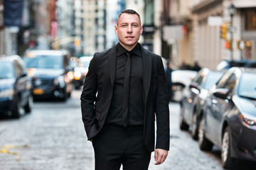 Fashionable businessman wearing black tie suit outfit walking on city street after working day