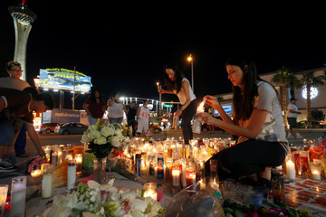 Apcar and her cousin light candles at a makeshift memorial for shooting victims at the Las Vegas Strip and Sahara Avenue in Las Vegas