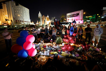 People gather at a makeshift memorial in the middle of Las Vegas Boulevard following the mass shooting in Las Vegas