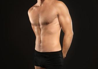 Young man in underwear on black background