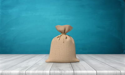 3d rendering of a blank tied up hessian bag full of money standing on a wooden surface on blue background.