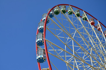 Big and modern multicolour ferris wheel on clean blue sky background