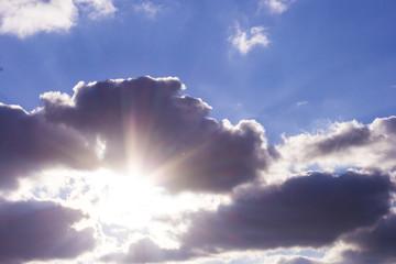 the sun shines through dark clouds