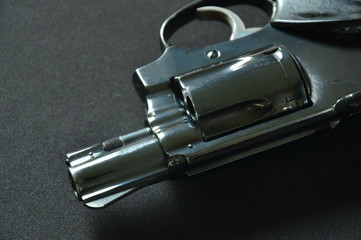 revolver gun on black fabric background