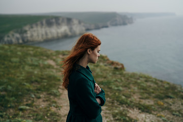 a woman is standing on a cliff near the sea and her hair is fluttering in the wind