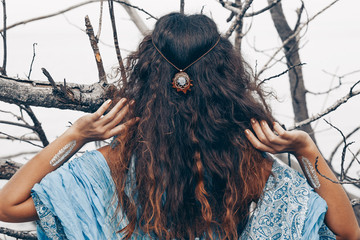 beautiful young woman posing from the back outdoors. witch craft esoterics concept