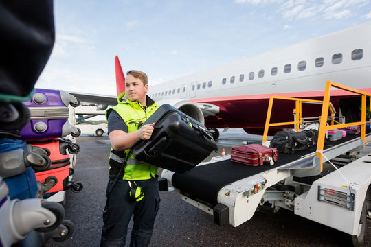 Worker Stacking Bags On Trailer At Runway