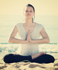 Young girl in white T-shirt is sitting and doing meditation