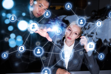Two business persons in front of futuristic display. Social networking concept.