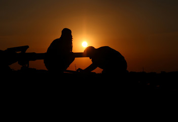 Free Syrian Army fighters are seen during sunset in the rebel-held area, in the town of Dael