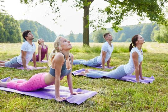 Leute machen Yoga Übung im Park